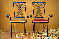 Two chairs, yellow plaster wall and dead leaves, Canmore Alberta Canada