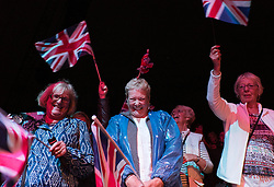 © Licensed to London News Pictures.22/08/15<br /> Castle Howard, North Yorkshire, UK. <br /> <br /> A group of friends wave flags and enjoy the evening as they attend the 25th anniversary of the Castle Howard Proms event near York. The theme of the event this year is a commemoration of the 75th anniversary of the Battle of Britain and the 70th anniversary of VE day and brings an evening of classic musical favourites celebrating Britishness to the lawns of Castle Howard.<br /> <br /> Photo credit : Ian Forsyth/LNP