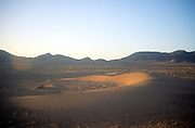Lens flare early morning an arc shaped barchan sand dune, Sahara desert, Zagora, Morocco