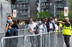 """© Licensed to London News Pictures. 25/06/2021. LONDON, UK.  People queue up to receive a first dose of the Pfizer vaccine at a pop-up mass vaccination clinic Arsenal's Emirates Stadium as part of a """"Gunner Get Jabbed"""" event organised by Islington Council, the local GP federation and the football club.  The NHS is also promoting a number of walk-in clinics this weekend across the capital to try to increase the number of over 18s receiving a jab as cases of the Delta variant are reported to be on the rise.  Photo credit: Stephen Chung/LNP"""