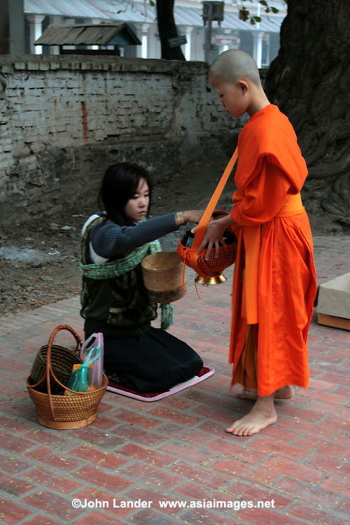 Young Novice Collecting Alms - In Buddhism, giving alms is a show of respect given by a lay Buddhist to a Buddhist monk. It is not charity as presumed by Western eyes. It is closer to a symbolic connection to the spiritual and to show humility and respect.  The visible presence of monks is a stabilizing influence in Lao society. The act of alms giving connects lay people to monks, what he represents and to Buddhism itself.