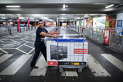 © Licensed to London News Pictures . 27/11/2015 . Salford , UK . A man wheeling a stock trolley loaded with televisions , vacuum cleaners and printers from a branch of Tesco in Pendleton , Salford , this morning (Friday 27th November) as people behind queue for Black Friday offers . Last year (2014) scuffles and fights were reported amongst queuing bargain-hunters . Photo credit: Joel Goodman/LNP