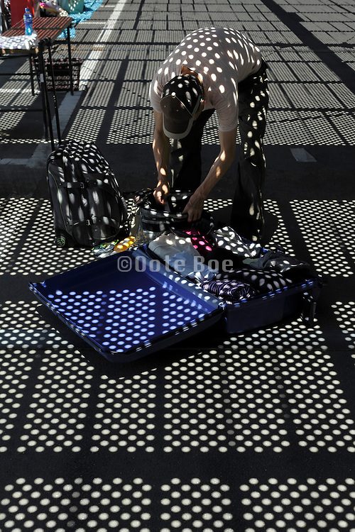 person packing a suitcase with grating shadow projection