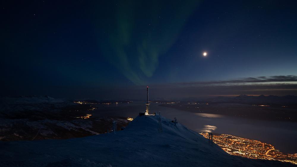 Nordlys som nærmest ser ut til å strømme fra tv-tårnet 'Linken' på Fagernestoppen i Narvik.