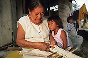 MACUXI INDIGENOUS PEOPLE, Amazon, near Boavista, northern Brazil, South America. Macuxi indian weaving traditional cotton cloths. Grandmother with children watching. Ecological biosphere and fragile ecosystem where flora and fauna, and native lifestyles are threatened by progress and development. The rainforest is home to many plants and animals who are endangered or facing extinction. This region is home to indigenous primitive and tribal peoples including the Yanomami and Macuxi.