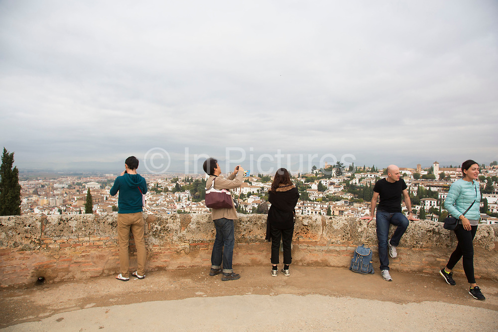 The Alhambra Palace and fortress complex located in Granada, Andalucia, Spain. Tourists at the tallest section and military watchtower, The Alcazaba.