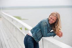 beautiful teenage girl leaning on a railing by the bay in East Hampton, NY