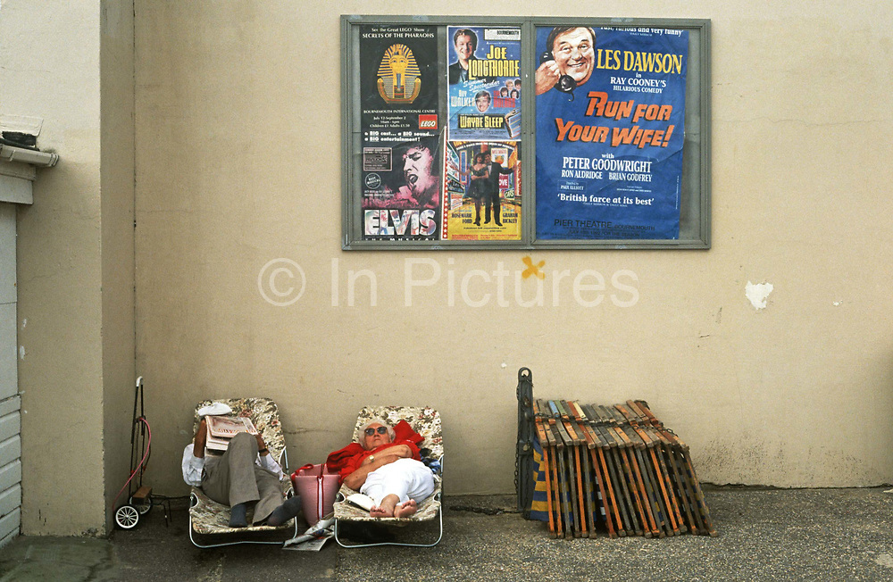 """A holiday couple sleep on portable beds in a particularly shabby corner of Bournemouth, a seaside resort in southern England. Above them are posters for this seedy part of the seaside resort on the south coast. Stars appearing in the summer season are an Elvis impersonator and the comedians Joe Longthorne and Les Dawson, who is appearing in Ray Cooney's show called """"Run For Your Wife!"""" The couple lie on their fold-up chairs, stretched out in a quiet corner below peeling plaster walls and beside a chained-up stack of deck chairs. The scene is a quintessentially English resort town that many from the 60s and 70s recall, when the Spanish package holiday suddenly became more attractive options, than the domestic week at home."""
