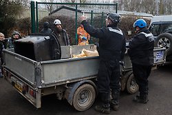 Harefield, UK. 13 January, 2020. Enforcement agents liaise with Stop HS2 activists during the construction of a gate across a public right of way leading to an activist protection camp. Part of the nearby Colne Valley protection camp was evicted by bailiffs last week. 108 ancient woodlands are set to be destroyed by the high-speed rail link and further destruction of trees for HS2 in the Harvil Road area is believed to be imminent.
