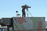 A soldier standing on top of a military command and control vehicle video taping the crowd at a protest