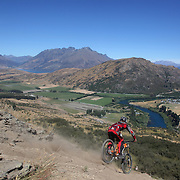 Sam Perry from  Leeston in action during the New Zealand South Island Downhill Cup Mountain Bike series held on The Remarkables face with a stunning backdrop of the Wakatipu Basin. 150 riders took part in the two day event. Queenstown, Otago, New Zealand. 9th January 2012. Photo Tim Clayton