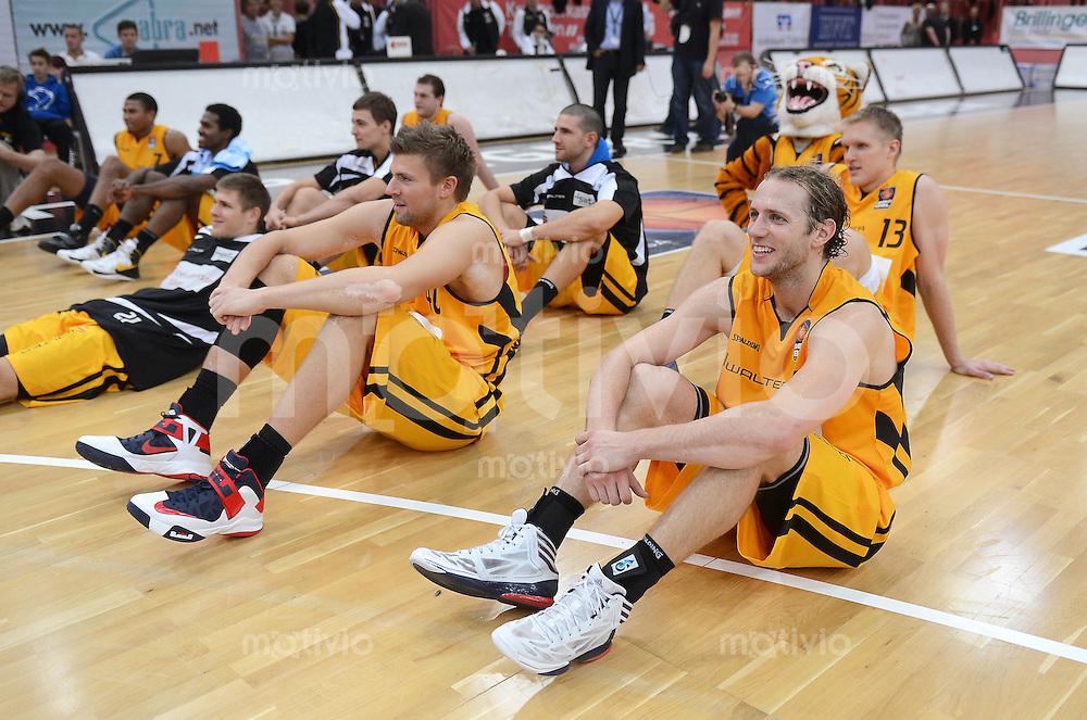 Basketball 1. Bundesliga   2012/2013  20.10.2012 Walter Tigers Tuebingen - LTi Giessen 46ers Tigersteam beobchtet im Sitzen die Schlussaktion der Fans; Machtwinner Vaughn Duggins (vorn re)