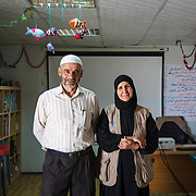 Abu Shadee, 52, on the right, and Um Shadee, 50, on the left, are in the the caravan where Um Shadee teaches knitting to girls in an adolescent friendly space. They fled Homs, Syria more than a year ago. They left so quickly that they brought nothing with them but the clothes on their backs.  Two of their seven children are with them now, but the other five are married and remained in Syria.  <br /> <br /> Azraq camp for Syrian refugees, Jordan, May 2015.