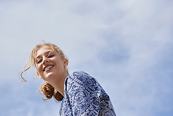 Low angle view of a young woman smiling, Munich, Bavaria, Germany