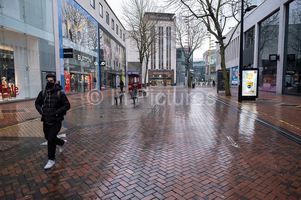National coronavirus lockdown three begins on New Street in Birmingham city centre, which is deserted apart from a few people wearing face masks in an area which is normally busy with shoppers on 6th January 2021 in Birmingham, United Kingdom. Following the recent surge in cases including the new variant of Covid-19, this nationwide lockdown, which is an effective Tier Five, came into operation today, with all citizens to follow the message to stay at home, protect the NHS and save lives.