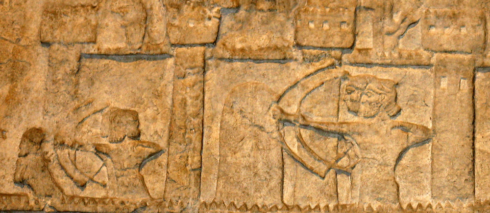 Detail from Assyrian palace decoration. Carved reliefs in walls that would have originally been in the interior of a palace. Depicting hunting, battle and religious scenes.