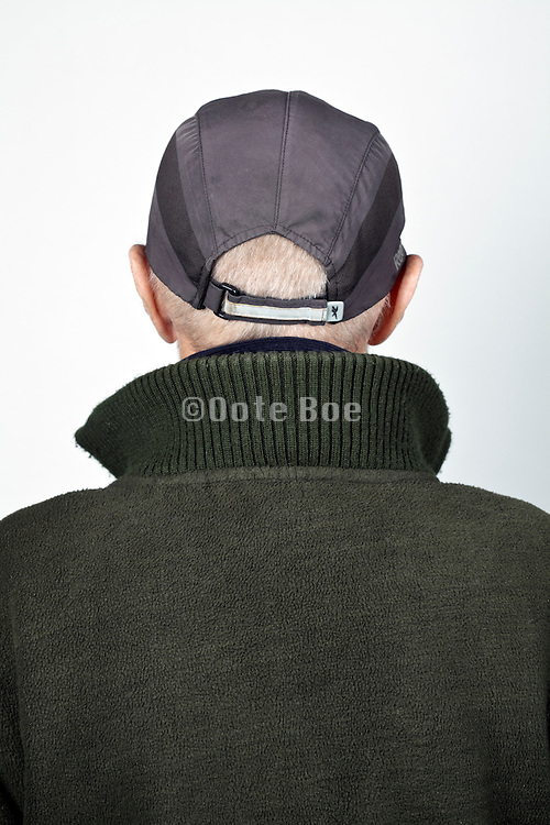 back view portrait 70 year of age person wearing a baseball cap