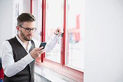 Young man office window using Smartphone