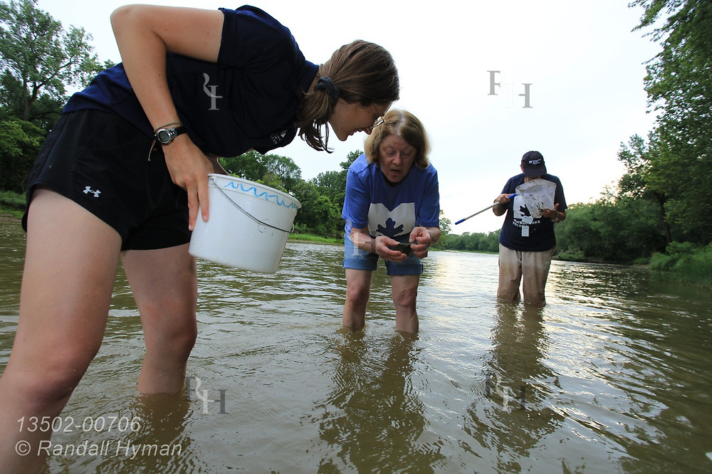 Emily Reutter of Metroparks Toledo helps volunteers collect tiny aquatic organisms to assess water quality of Maumee River at Side Cut Metropark, Maumee, Ohio.