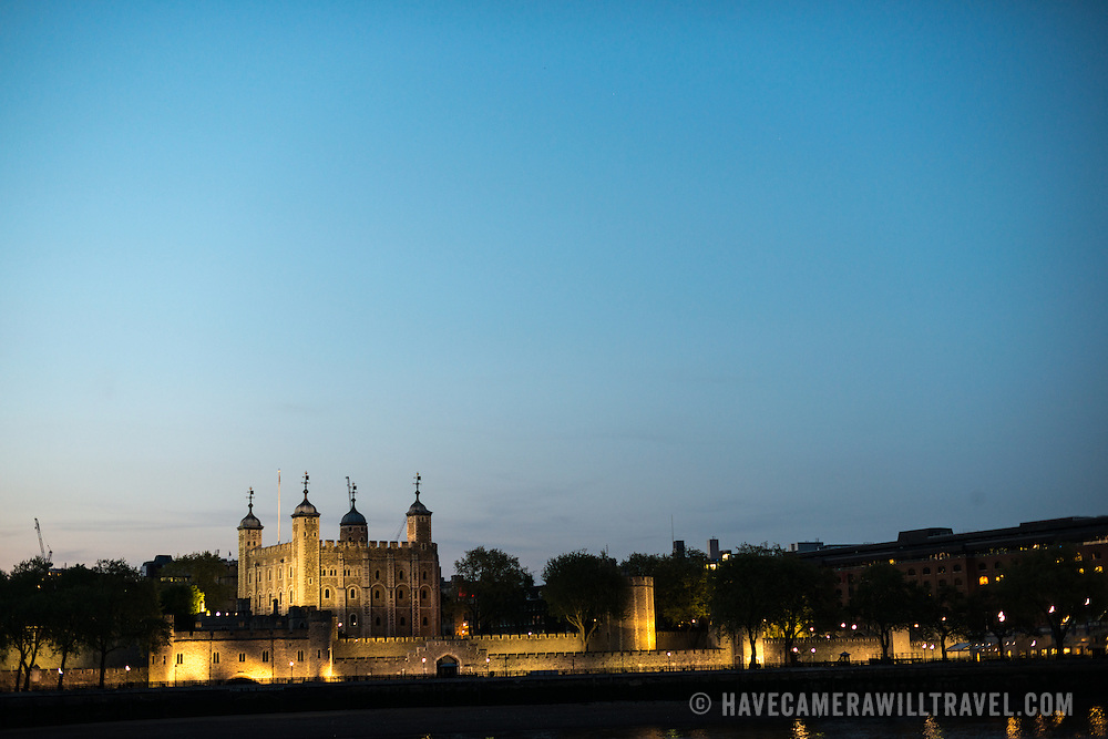 The Tower of London illuminated by lights against the dusk sky, as seen from the southern bank of the Thames. With copyspace.