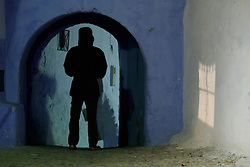People walking through blue archway at night, Chefchaouen, Morocco