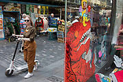 On a corner of Berwick Street in Soho at the end of the market, the shop window of Gosh Comics graphic novel and comic book store interracts in light with passers by in a colourful street scene in London, United Kingdom.
