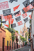 Domes and spires of the Parroquia San Miguel Arcangel church seen through paper banners called papel picado strung to celebrate the Day of the Dead festival on Aldama Street in the historic district of San Miguel de Allende, Mexico.