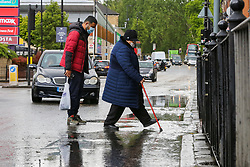 © Licensed to London News Pictures. 24/05/2021. London, UK. An elderly woman wearing a face covering walks through a large puddle of water in north London, with more rain forecast for the South East of England today. Over the May bank holiday, temperatures are expected to reach 21 degrees celsius. Photo credit: Dinendra Haria/LNP