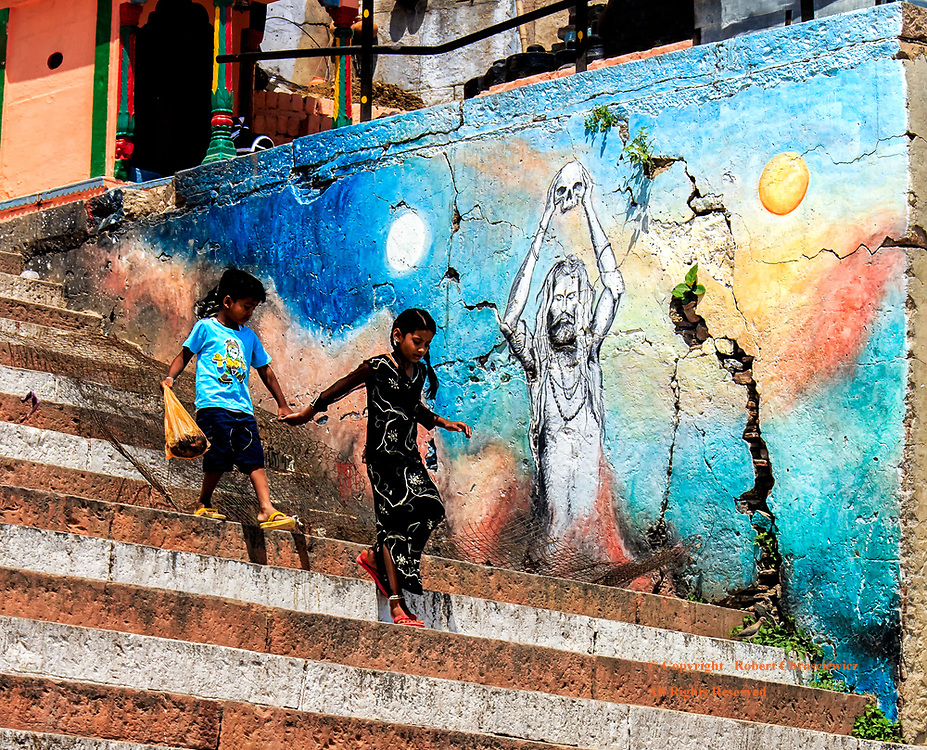 A pair of young children descends the white and red stairs, passing a colourful wall painting of a naked Hindu Sadhu holding onto a skull overhead, en-route to the holy Ganges, Varanasi India.