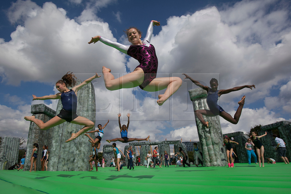 © licensed to London News Pictures. London, UK 21/07/2012. Three girls from Camden Gymnastics Squad posing on Jeremy Deller's life-size bouncy castle version of Stonehedge, entitled Sacrilege which comes to London as a part of the London 2012 Festival on 21/07/12. Photo credit: Tolga Akmen/LNP