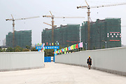 Workers walks through the construction yard at Huadian Stars City in Yangzhou, Jiangsu Province, China on 19 July 2012. While the Chinese government has tried various ways to cool down the property market, real estate prices have still seen a steady increase in recent years, proving hard for the country to move away from an investment driven economy.