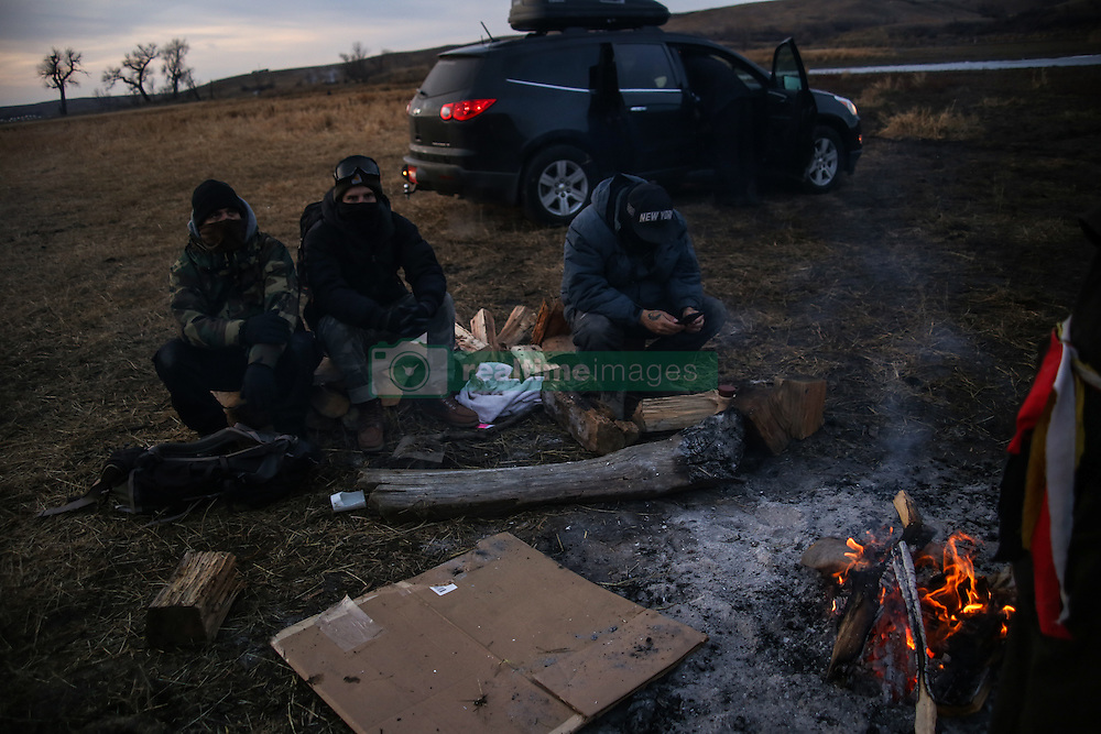 November 25, 2016 - Cannon Ball, North Dakota, U.S - Water protectors sit by a campfire near Turtle Island after finding out that authorities placed barbed wire along the Missouri River blocking access to a sacred burial site near the Oceti Sakowin Camp at the Standing Rock Indian Reservation in Cannon Ball, North Dakota. (Credit Image: © Joel Angel Ju‡Rez via ZUMA Wire)