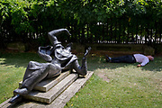As heatwave temperatures climb to record levels - the hottest day of the year so far - a Londoner sleeps in the shade next to the sculpture entitled Becket by Bainbridge Copnall 1973, in the City of London the capitals financial district aka the Square Mile during a hot lunch-hour in St. Pauls Cathedral Churchyard, on 25th July 2019, in London, England.