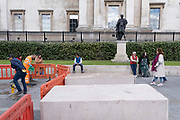Work contractors clean paving stones alongside a pointing statue of King James II as Roman Emperor in Trafalgar Square, on 14th October, 2021, in Westminster, London, England.