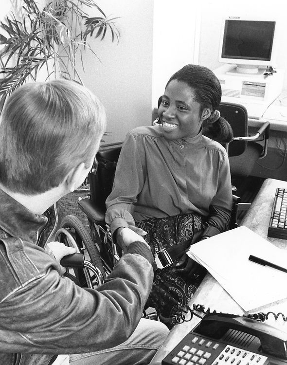©1994 Handicapped woman, late 20's working in small business and interviewing customer  PR EP-0119 color available.