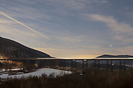 A train crosses the Moodna Viaduct railroad trestle heading toward Schunnemunk Mountain in Cornwall, N.Y., on Dec. 19, 2020. The conjunction of Jupiter and Saturn is visible above Woodcock Mountain, at right. Lights from a passing car on Otterkill Road, at left, show as streaks in the combination of long expsure images.