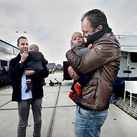 Nederland, Amsterdam , 1 oktober 2014.<br /> De rij caravans met mensen die een zelfbouwkavel willen kopen op het Zeeburgereiland wordt steeds groter.<br /> Sommige staan al een paar weken in de wachtrij totdat ze een kavel mogen kopen. Pas volgende week zaterdag gaan de kavels pas in de verkoop, maar wie weg gaat, verliest zijn plek in de rij.<br /> Een van de kampeerders staat er al een tijdje in zijn caravan: 'Ik ben hier behoorlijk vroeg gaan staan, want er is één kavel waar ik echt geïntresseerd in ben. Er hoeft er maar een eerder te zijn en dan ben je 'm kwijt.'<br /> De wachtende kopers vinden het best gezellig op het terrein: 'Je ontmoet een soort van je toekomstige buren als het zo doorgaat. Dat geeft een apart campinggevoel en we barbecuen samen.'<br /> Een probleempje, als je weggaat ben je je plek kwijt. 'Als je moet werken moet je zorgen dat er iemand anders op je plek zit. Ik had hier eerst helemaal geen zin in, maar het is toch wel een bizar avontuur.'<br /> Op de foto: 2 kavelkopers en hun kinderen.<br /> Foto:Jean-Pierre Jans