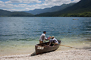 A baby is passed into a rowing boat at a shore of Lake Bohinj near Ucanc, on 19th June, in Lake Bohinj, Sovenia.