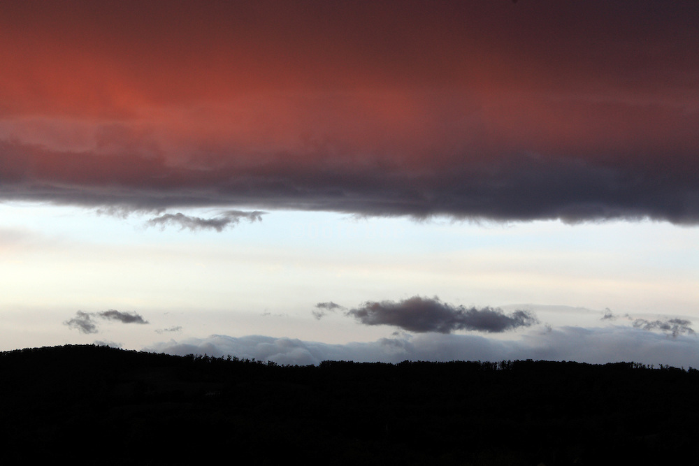 dramatic cloud formation contrasting with a silhouette hilly landscape