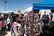 """With the church in the distance. The gitan gypsy market, next to the Town Hall, sells all sorts of colourful and garish items for everyone. From toy guitars and T-shirts depicting the new French Gypsy star 'Kenji' to stoves and tent pegs<br /><br />""""Le Pelerinage des Gitans""""; the French gypsy pilgrimage of Saintes Maries de la Mer, Camargue, France<br /><br />Sainte Sara is an uncannonized saint, who legend says looked after the Christian Saints Marie Jacobe and Marie Salome, cousins of Mary Magdalene, who arrived, it is said, on the shores of the Camargue in a rudderless boat. Saint Sara is the patron saint of gypsies who come from far and wide to see her. There are even paintings of Sara as 'Kali' the black saint in Eastern Europe. Sara may have been the priestess of 'Ra' the sun-god or even servant girl to the Christian saints. No-one really knows.<br /><br />For a few weeks of the year, Roma, Gitan and Manouche gypsies come from all over Europe in May, camping in caravans around Saintes Maries de la Mer. It is a festive time where they play music, dance, party and christen their children. They all go to see Saint Sara in the crypt, kissing or touching her forehead. Many put robes on her shoulders, making her fat for the procession. In the main Gypsy procession of the 24th May, Saint Sara is allowed to leave her crypt, beneath the church, and is carried from the church to the shores of the mediterranean and back again. One day a year she is free from her prison. Hundred's of years ago the Gypsies used not even to be allowed into the church, only into the crypt like Sara...<br /><br />Roma gypsies still suffer oppressive prejudice and racism and are one of the ethnic groups the most persecuted and marginalised across Europe. The festival is one of the times where they celebrate with people of all races, their faith and traditions"""