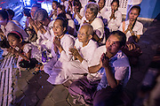 """04 FEBRUARY 2013 - PHNOM PENH, CAMBODIA:  Cambodians pray on a street corner in Phnom Penh during the cremation of their former King Norodom Sihanouk during the King-Father's cremation service in Phnom Penh. Norodom Sihanouk (31 October 1922- 15 October 2012) was the King of Cambodia from 1941 to 1955 and again from 1993 to 2004. He was the effective ruler of Cambodia from 1953 to 1970. After his second abdication in 2004, he was given the honorific of """"The King-Father of Cambodia."""" Sihanouk died in Beijing, China, where he was receiving medical care, on Oct. 15, 2012.   PHOTO BY JACK KURTZ"""
