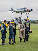 Re-enactors in World War II uniforms on the flight line watching a Hawker Nimrod -  - The Duxford Battle of Britain Air Show is a finale to the centenary of the Royal Air Force (RAF) with a celebration of 100 years of RAF history and a vision of its innovative future capability.