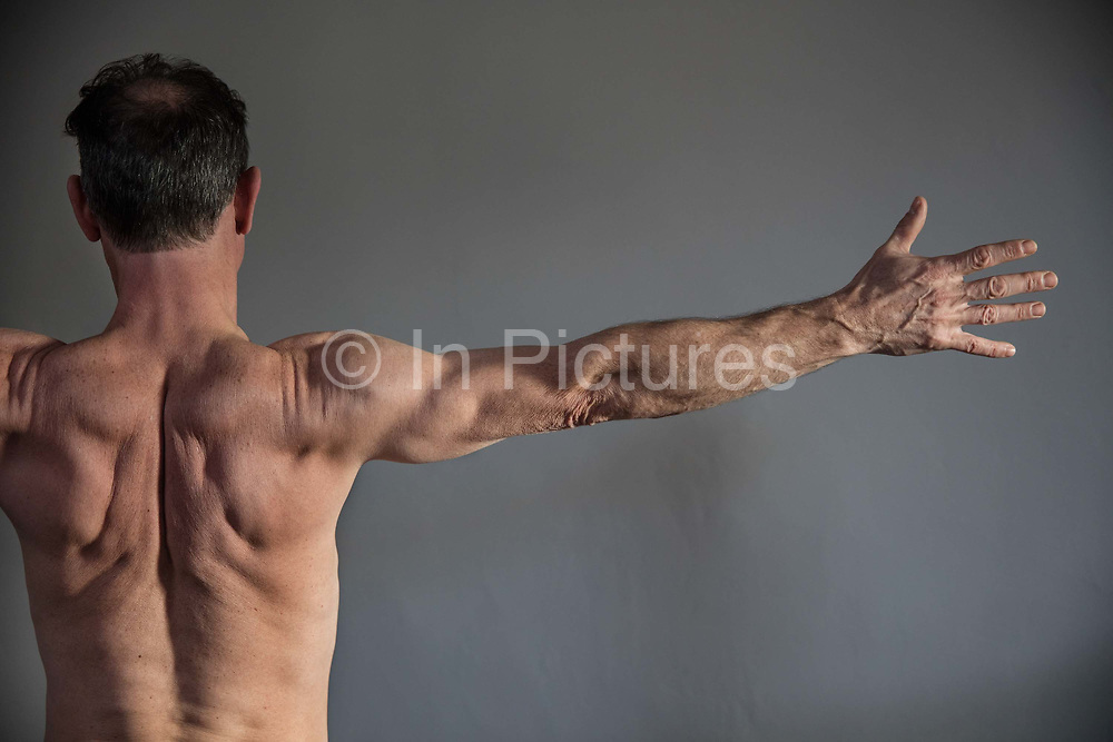 Close up showing the muscles on the back of a middle aged man keeping fit with yoga on 29th December 2016, Lagrasse, France.