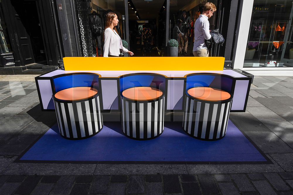 """© Licensed to London News Pictures. 14/09/2019. LONDON, UK.  People pass a sculptural bench as """"Walala Lounge"""" opens in Mayfair's South Molton Street.  Artist and designer Camille Walala's installation comprises 10 sculptural benches, accompanied by planters and a series of oversized flags strung, bunting-style, from shopfront to shopfront, converting the street into an immersive corridor of colour as part of this year's London Design Festival.  Photo credit: Stephen Chung/LNP"""