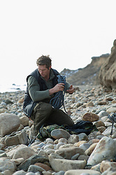 man on a rocky beach in Montauk setting up a campsite