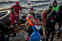 MYTILINI, GREECE - FEBRUARY 09: A volunteer holds a young boy after his arrival at Katia beach in a dinghy during the early morning on February 09, 2015 in Mytilini, Greece. Dozens of volunteers watch day and night on the beaches of Lesvos for the arrival of refugees. Volunteers are the firsts to help refugees that are not rescued by coastguards that watch the Aegean sea. Teams of doctors from different countries work together with international rescue teams in providing assistance to the hundreds of refugees arriving at the beaches of Lesvos, guiding dinghies to safe arrival areas, providing hot drinks and food, shoes, clothes and medical assistance to those arriving sick. Hypothermia is a common symptom on the refugees arriving at Lesvos after crossing the Aegean sea for more than 2 hours from the Turkish coast, from where they are smuggled into Europe. Photo: © Omar Havana. All Rights Are Reserved