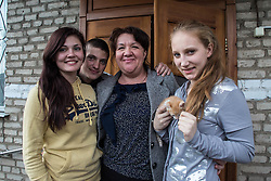 Elena, 17, (l) and Diana, 17, (r) with kitten. Elena has been a resident of Lugansk Orphanage No.1 since the age of three. The kitten is a present from her boyfriend Sergey, 22. They pose with Victoria Mochalova Alexandrovna, the director of the orphanage.