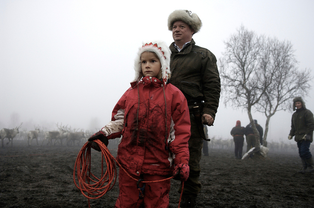 A father and his 7-year-old daughter scan the galloping reindeer in search of their calves. The Sami herding lifestyle struggles to maintain its force in numbers with lower wages and a demanding work schedule. Very few youth seek a future as a full time herder.  Despite the inhospitable Arctic climate reindeer herding has been the livelihood of the Sami for hundreds of years, but amid the economic, technological, and environmental problems of modern society their indigenous culture must increasingly reconcile these radical changes in order to preserve age-old traditions, customs, and mores.