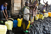 A boy waits to have his jerican filled with water from a water tank in Goma, Eastern Democratic Republic of Congo on Monday December 15, 2008. Goma's Majengo neighborhood is almost entirely built on lava, after the nearby volcano erupted in 2002. As a result, there is no working water supply network, and residents, often children, must sometimes walk several kilometers to go buy water from tanks spread around the area.
