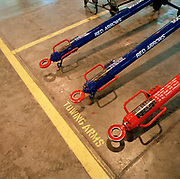 Towing bars on the ground in the hangar of the Red Arrows, Britain's RAF aerobatic team. Seen from above in the hangar at RAF Scampton the team's base (but once the hangars of the famous Dambusters 617 Squadron), the engineering specialists called the Blues perform routine maintenance in the Red Arrows team hangar. They are ground-based back-up crew (so-called after their distinctive blue overalls worn only during the summer) and perform routine engineering tasks in the hangar at RAF Scampton, then while on tour, keeping the jets serviceable and ready to display. The Blues outnumber the pilots 8:1. Without them, the Red Arrows couldn't fly. Some of the team's Hawks are 25 years old and their air frames require constant attention, with increasingly frequent major overhauls due.